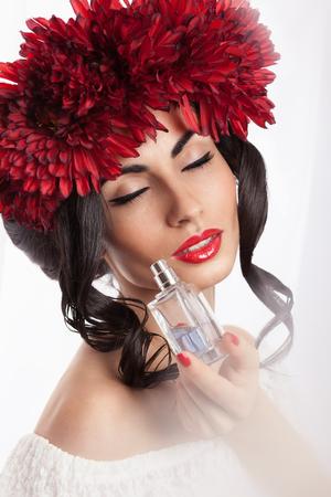 Fashionable model smelling a perfume on white background photo