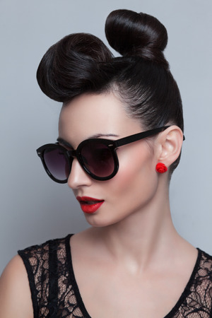 Fashionable model in trendy sunglasses. Plastic skin. Portraiture. Red lips. Updo, twisted high bun. top knot