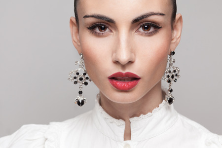 Headshot of fashionable model with perfect makeup and hairstyle. red lips, white shirt. big earrings photo