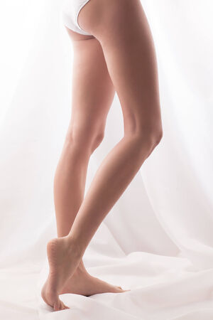 varicose veins: Barefoot girl posing. High key shot