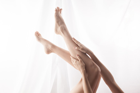 Lying woman stroking feet. high key Stock Photo