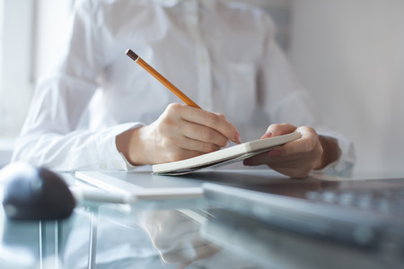 메모장에 지적 연필을 사용하는 여자의 손