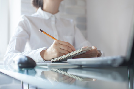 businesswoman writing with pencil on notepad in the office Archivio Fotografico