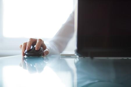 유리 테이블에 무선 마우스를 사용 여자의 손
