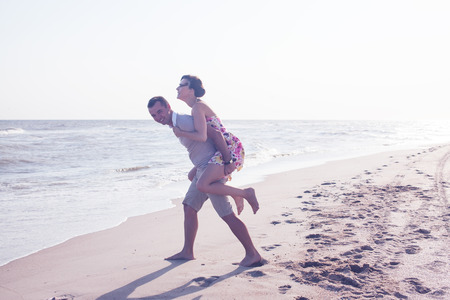 Portrait of man carrying girlfriend on his back photo