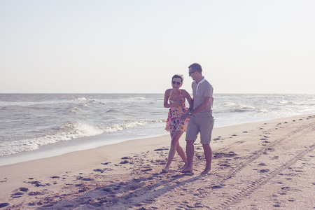 Dynamic shot of happy smiling couple. Focus on guy. Walking on the beach. Holding each other and laughting