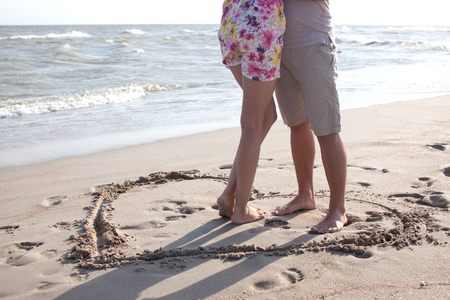 feet in sand: Couple legs standing inside heart picture on the sand. Summertime fun