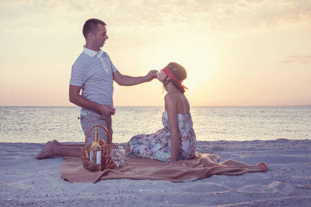 hamper: Young man feeding chocolade candy his girlfriend with covered eyes during sunset on beach
