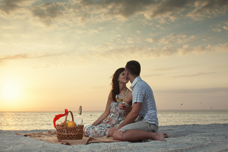 Pár na pláži s Luxury Wine piknik během krásný západ slunce. Svítání Reklamní fotografie