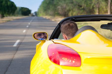 젊은 사람이 자신의 컨버터블 노란색 차를 운전의 다시보기. 오픈 지붕