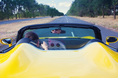 Male driver steering convertible car with open roof   Back view Reklamní fotografie