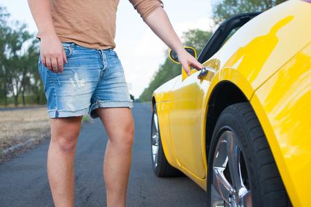 yellow car: Closeup of Young Man open covertible cars door  Yellow car  Brown t-shirt, jeans shorts