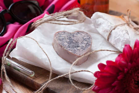 Bar of homemade soap with orange and loofah  Aromatized Scrub soap  A heart shape photo