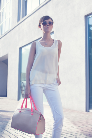 Trendy girl in sunglasses.beige blouse. white shirt. beige leather bag. high heels photo