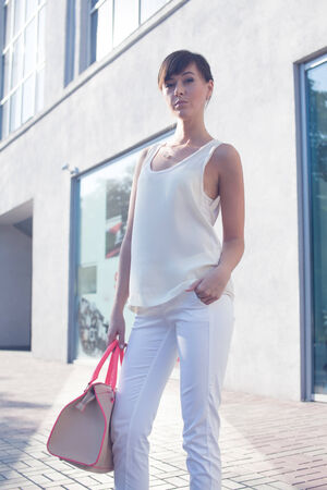 Brunette Model posing near the mall.beige blouse. white shirt. beige leather bag. high heels photo