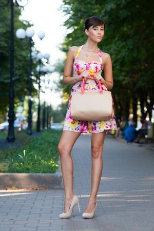 Gelukkig mooi model staande op street.flowered witte jurk .beige lederen handtas. hoge hakken Stockfoto