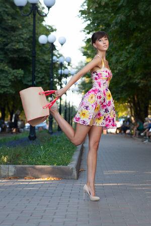 Happy beautiful model jumping on street.flowered white dress .beige leather handbag. high heels photo