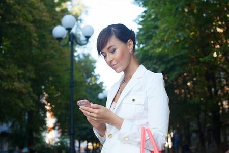 Beautiful model in white jacket  dealing phone number on the street photo