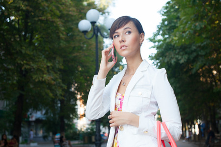 Beautiful young business woman in white jacket  talking on phone on the street photo