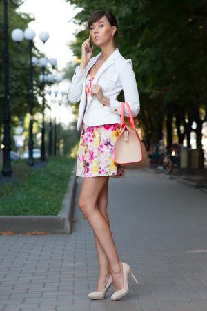 Sexy jonge zakenvrouw praten over de telefoon op de straat. bloemrijke witte jurk .beige lederen handtas. hoge hakken