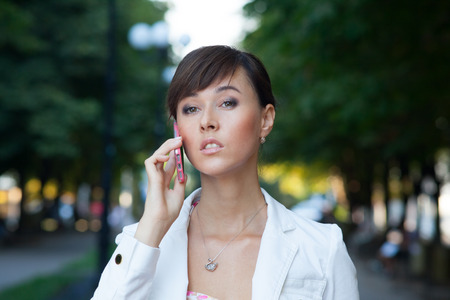 Closeup portrait of beautiful young business woman in white jacket  talking on cellphone on the street photo