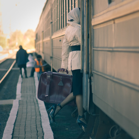 Fashionable woman entering inside train car. Holding a suitcase photo