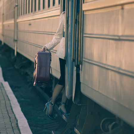 Fashionable woman entering into train car. Holding a suitcase photo