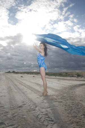 Full growth portrait of young lady with long blue material and exclusive dress. Stormy and cloudy weather photo