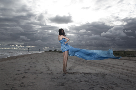 Caucasian model posing on the beach with long dress  Stormy sunset photo