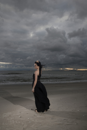 Brunete woman posing on seashore in black long dress photo