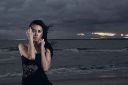 Close up portrait of brunete model in black dress on the empty beach. Cloudy sunset