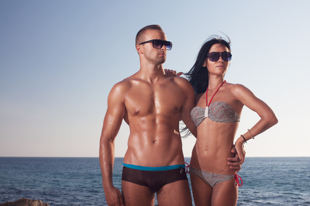 passionate couple in sunglasses lying on the sea shore  perfect body and sporty couple  bodybuilders outdoors Reklamní fotografie