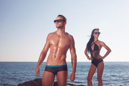 Sportieve man toont zijn perfect geolied lichaam Meisje achter