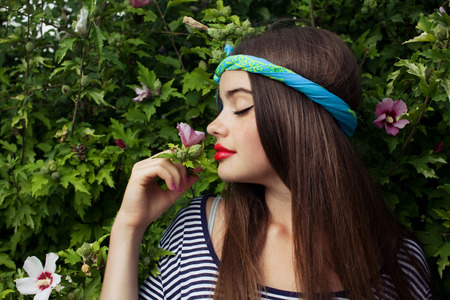 trendy teenager model with kerchief posing on flowers BG photo
