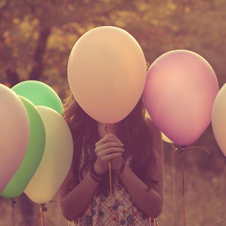 Dívka schovává za balónem