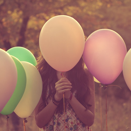 Girl hiding behind the balloon photo