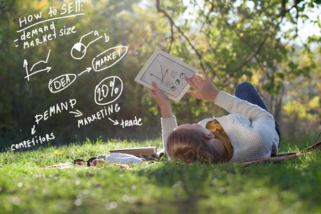 Liggende vrouw tekenen business concept op tablet pc scherm tijdens rust in het park Stockfoto