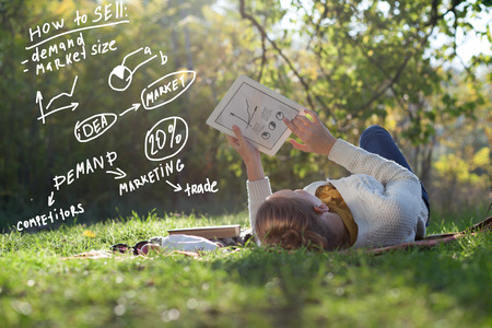 Lying woman drawing business concept on tablet pc screen during rest in the park