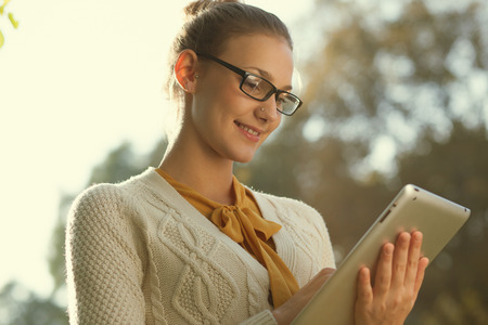 woman in glasses using tablet pc in the park