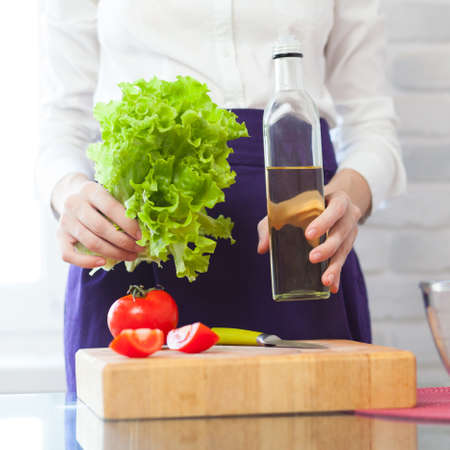 Woman hands holding a salad and olive oil bottle photo