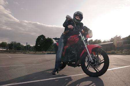 biker in helmet posing on motorbike