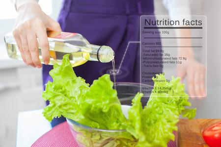 Nutrition facts of Olive oil. Female hand holding olive oil bottle