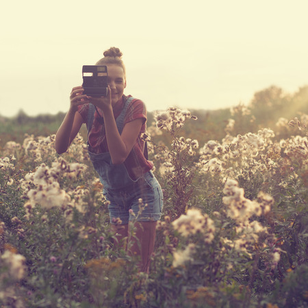fashion photography: Girl photographer taking photo in the field Stock Photo