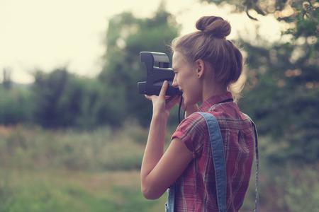 Girl photographer shooting outdoors photo