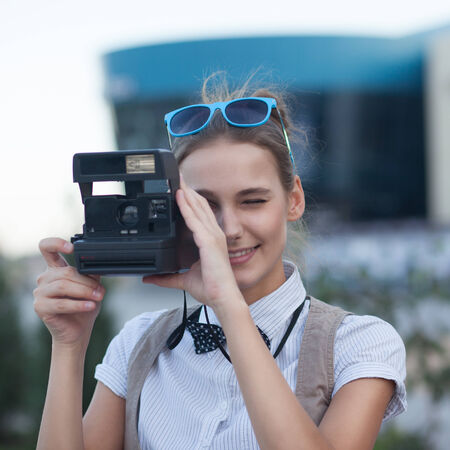 Stylish girl taking a photo in the city photo
