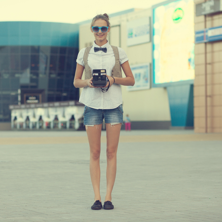 hipster girl posing with instant camera photo