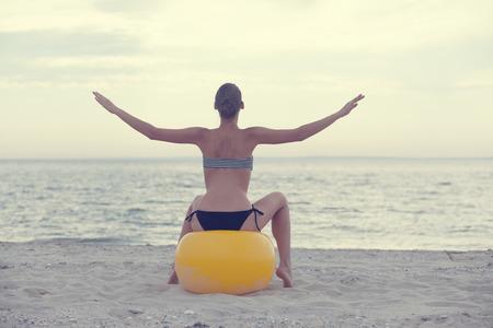 pilates ball: girl sitting on yoga ball outdoors
