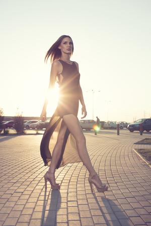 긴 검은 드레스에 산책하는 여자