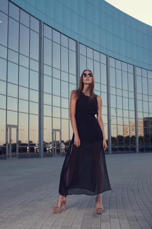 Full growth portrait of fashionable woman on urban background photo