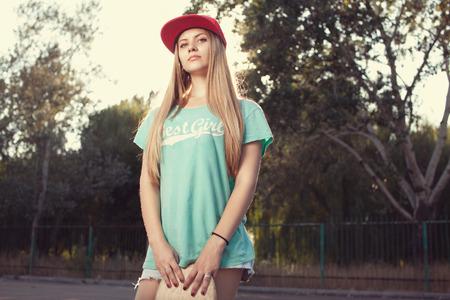 Teen model posing with skateboard Standard-Bild